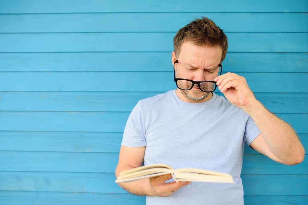 Man reading book putting glasses on